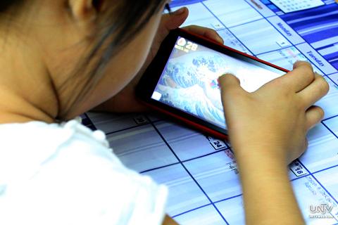 FILE PHOTO: Isang batang naglalaro ng isang smartphone game (PHOTOVILLE International)