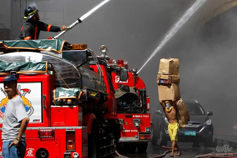 Ang mga kawani ng Bureau of Fire Protection habang inaapula ang apoy sa Divisoria mall na hanggang sa ngayon ay nasusunog pa rin. (PHOTOVILLE  INTERNATIONAL)