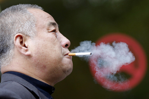 "A man smokes next to a ""No Smoking"" sign in Shanghai. China is the largest consumer of tobacco. Photo: Reuters"