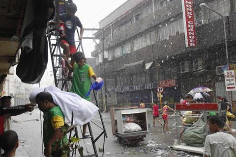 Ang ilan sa mga residente sa Tacloban City na nangloob sa mga establisyimento upang makakuha ng mga bagay na kanilang mapapakinabangan nitong Linggo, Nobyembre 10, 2013.  (REUTERS / Romeo Ranoco)