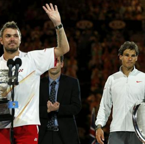 Stanislas Wawrinka of Switzerland waves with the Norman Brookes Challenge Cup as Rafael Nadal of Spain (R) reacts in their men's singles final match at the Australian Open 2014 tennis tournament in Melbourne January 26, 2014.  REUTERS/Jason Reed