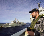 Able Seaman Maritime Logistics Steward Kirk Scott keeps watch aboard the Australian Navy ship HMAS Success as they conduct a replenishment at sea with HMAS Toowoomba while continuing to search for the missing Malaysian Airlines flight MH370, in this picture released by the Australian Defence Force April 11, 2014.  REUTERS/Australian Defence Force/Handout via Reuters