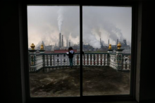 A girl reads a book on her balcony as smoke rises from chimneys of a steel plant, on a hazy day in Quzhou, Zhejiang province April 3, 2014. CREDIT: REUTERS/STRINGER