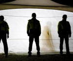 A family member of a missing passenger onboard the South Korean ferry Sewol is silhouetted as police officers stand guard outside a tent acting as a temporary morgue at a port, where family members of the missing passengers are gathered, in Jindo April 19, 2014. REUTERS/Issei Kato