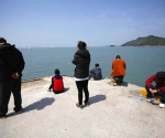 Family members of missing passengers who were on the South Korean passenger ferry Sewol which sank in the sea off Jindo, look towards the sea at a port where family members of missing passengers gathered, in Jindo April 21, 2014.  REUTERS/Issei Kato