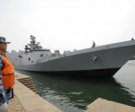 A Chinese navy personnel (L) stands guard as Indian naval frigate INS SHIVALIK is seen docked at a military port after its arrival before a maritime drill during the Western Pacific Naval Symposium in Qingdao, Shandong province, April 20, 2014. CREDIT: REUTERS/STRINGER