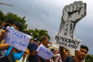 Demonstrators hold up signs during a protest against military rule at Victory Monument in Bangkok May 27, 2014. CREDIT: REUTERS/ATHIT PERAWONGMETHA