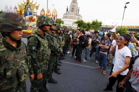 Protesters against military rule face soldiers at the Victory monument in Bangkok May 26, 2014. CREDIT: REUTERS/DAMIR SAGOLJ