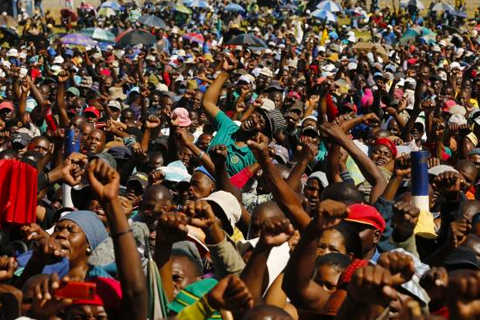 Lonmin workers on strike react as they listen to President of South Africa's Association of Mine workers and Construction Union (AMCU) Joseph Mathunjwa's (not in picture) speech at the Wonderkop stadium in Nkaneng township outside the Lonmin mine in Rustenburg May 14, 2014. CREDIT: REUTERS/SIPHIWE SIBEKO