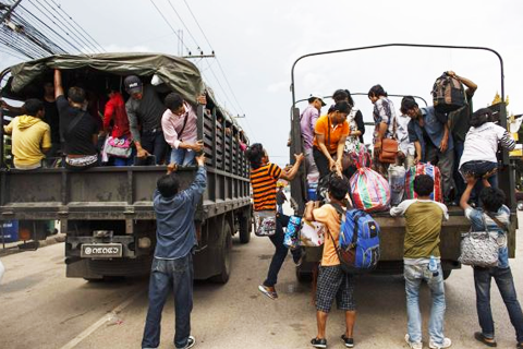 Cambodian workers ride on military trucks as they prepare to cross the Thai-Cambodia border at Aranyaprathet in Sa Kaew June 15, 2014. CREDIT: REUTERS/ATHIT PERAWONGMETHA