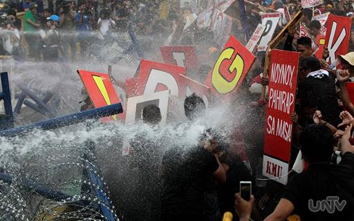 Binomba ng tubig ng Philippine National Police ang mga rallyistang ito sa Commonwealth Avenue, Quezon City kaugnay ng ikalimang SONA ni Pangulong Aquino. (Photoville International)
