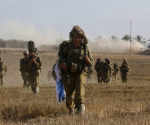 An Israeli soldier from the Givati Brigade walks back to a staging area after returning to Israel from Gaza July 30, 2014. The Israeli military said on Wednesday it would hold fire unilaterally in limited areas of the Gaza Strip for four hours from 3 p.m. (1200 GMT) for humanitarian purposes, an army statement said. Hamas described the truce as a media stunt because it only applied to some areas.  REUTERS/Baz Ratner