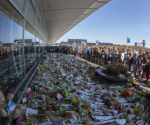 Flight attendants and mourners gather near flower bouquets as they pay their respects at Schiphol Airport during a national day of mourning for the victims of the downed Malaysia Airlines flight MH17, in Schiphol July 23, 2014.  REUTERS/Cris Toala Olivares