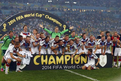 Germany's players pose for pictures as they celebrate with their World Cup trophy after winning their 2014 World Cup final against Argentina at the Maracana stadium in Rio de Janeiro July 13, 2014