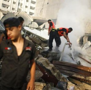 A Palestinian firefighter puts out a fire at the remains of a tower building housing offices, which witnesses said was destroyed by an Israeli air strike, in Gaza City August 26, 2014. CREDIT: REUTERS/MOHAMMED SALEM