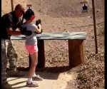 Shooting instructor Charles Vacca stands next to a 9-year-old girl at the Last Stop shooting range in White Hills, Arizona near the Nevada border, on August 25, 2014, in this still image taken from video courtesy of the Mohave County Sheriff's Office. CREDIT: REUTERS/MOHAVE COUNTY SHERIFF'S OFFICE/HANDOUT VIA REUTERS