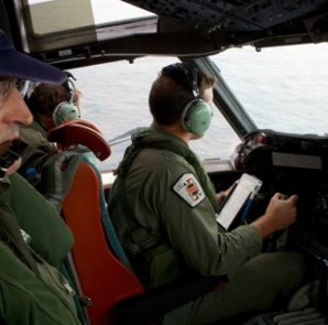 Co-Pilot, Flying Officer Marc Smith (R) and crewmen aboard a Royal Australian Air Force (RAAF) AP-3C Orion aircraft, search for the missing Malaysian Airlines Flight MH370 over the southern Indian Ocean in this March 24, 2014 file photo.  REUTERS/Richard Wainwright/Pool/Files