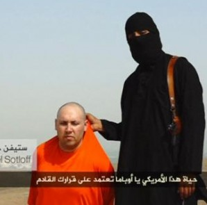 A masked Islamic State militant speaks next to a man purported to be U.S. journalist Steven Sotloff at an unknown location in this still image from an undated video posted on a social media website. CREDIT: REUTERS/SOCIAL MEDIA WEBSITE VIA REUTERS TV