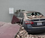 A car damaged by bricks falling during an earthquake is seen next to a downtown building in Napa, California August 24, 2014.  CREDIT: REUTERS/STEPHEN LAM