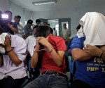 Filipino suspects of a foiled bomb attack (L-R) Sonny Yohanon, Emmanuel San Pedro and Grandeur Pepito Guerrero, cover their faces during inquest proceedings inside the Department of Justice in Manila, Philippines, 02 September 2014. Philippine authorities blamed a foiled bomb attack at the capital's international airport on a group allegedly frustrated over how the government was dealing with territorial disputes with China. The three suspects were arrested in the carpark of Terminal 3 at the Ninoy Aquino International Airport in Manila. Homemade incendiary bombs made from large firecrackers and gasoline were seized from their vehicle. (PHOTOVILLE INTERNATIONAL)