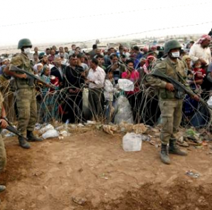 Turkish soldiers stand guard as Syrian Kurdish refugees wait behind the border fences to cross into Turkey near the southeastern town of Suruc in Sanliurfa province September 27, 2014.  CREDIT: REUTERS/MURAD SEZER