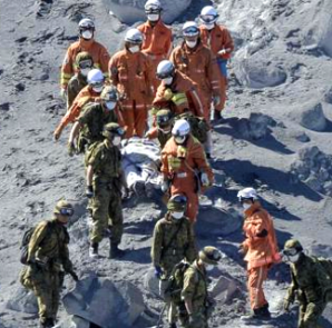 Japan Self-Defense Force (JSDF) soldiers and firefighters carry an injured person near a crater of Mt. Ontake, which straddles Nagano and Gifu prefectures in this September 28, 2014 photo taken and released by Kyodo.  REUTERS/Kyodo