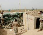 Members of the Kurdish security forces stand guard against Islamic State militants (background), behind sandbags on the Mullah Abdullah bridge in southern Kirkuk September 29, 2014. REUTERS/Ako Rasheed