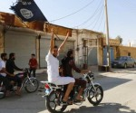A resident of Tabqa city touring the streets on a motorcycle waves an Islamist flag in celebration after Islamic State militants took over Tabqa air base, in nearby Raqqa city August 24, 2014. CREDIT: REUTERS/STRINGER