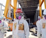Japan's new Economy, Trade and Industry Minister Yuko Obuchi (C), wearing a protective suit and a mask, inspects at the tsunami-crippled Fukushima Daiichi nuclear power plant in Fukushima prefecture September 7, 2014, in this photo released by Kyodo. Mandatory credit CREDIT: REUTERS/KYODO