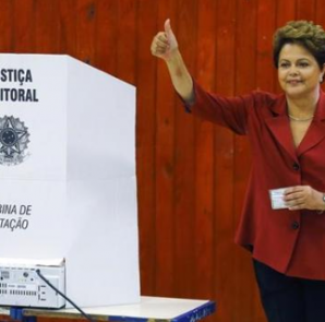 Brazil's President and Workers' Party (PT) presidential candidate Dilma Rousseff gestures to photographers after voting in the runoff election in Porto Alegre October 26, 2014. CREDIT: REUTERS/PAULO WHITAKER
