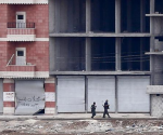 Kurdish fighters walk through a street in the Syrian town of Kobani, October 19, 2014.  CREDIT: REUTERS/KAI PFAFFENBACH