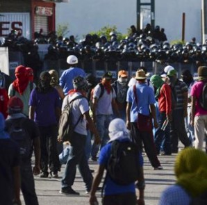 Students of the Ayotzinapa Teacher Training College ''Raul Isidro Burgos'' stand in front of riot police as they protest, demanding the government find 43 of their classmates missing since last month's deadly clashes, outside the City Hall in Chilpancingo, in the southern Mexican state of Guerrero, October 13, 2014. CREDIT: REUTERS/STRINGER