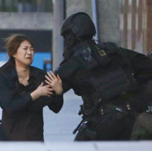 . A hostage runs towards a police officer outside Lindt cafe, where other hostages are being held, in Martin Place in central Sydney December 15, 2014.  CREDIT: REUTERS/JASON REED