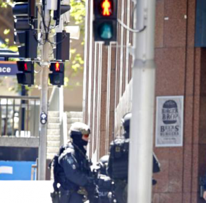 New South Wales state police officers are seen at a corner near Lindt cafe in Martin Place, where hostages are being held, in central Sydney December 15, 2014.  CREDIT: REUTERS/JASON REED