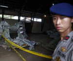 A police officer stands near part of the fuselage of crashed AirAsia Flight QZ8501 inside a storage facility at Kumai port in Pangkalan Bun, January 19, 2015. CREDIT: REUTERS/BEAWIHARTA