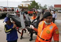 Rescue team members walk as they carry the wreckage of a seat of the AirAsia Flight QZ8501 airliner at Kumai port in Pangkalan Bun, January 19, 2015. CREDIT: REUTERS/BEAWIHARTA