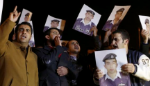 Relatives of Islamic State captive Jordanian pilot Muath al-Kasaesbeh hold up his pictures as they chant slogans demanding that the Jordanian government negotiate with Islamic state and for the More... CREDIT: REUTERS/MUHAMMAD HAMED