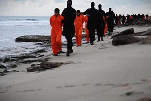 Men in orange jumpsuits purported to be Egyptian Christians held captive by the Islamic State (IS) are marched by armed men along a beach said to be near Tripoli, in this still image from an undated video made available on social media on February 15, 2015. CREDIT: REUTERS/SOCIAL MEDIA VIA REUTERS TV