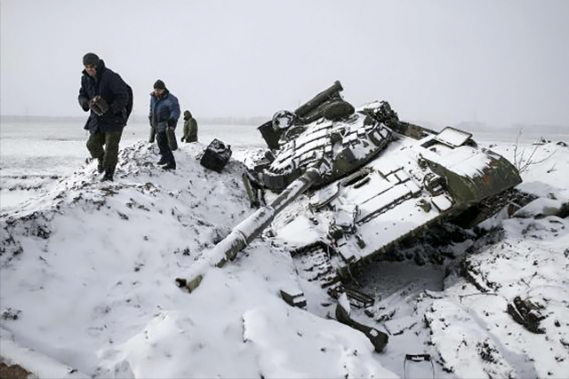 Members of the separatist self-proclaimed Donetsk People's Republic army collect parts of a destroyed Ukrainian army tank in the town of Vuhlehirsk, about 10 km (6 miles) to the west of Debaltseve, More... CREDIT: REUTERS/BAZ RATNER