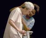 A nurse helps an elderly woman in a walker in a handout photo. CREDIT: REUTERS/NEWSCOM