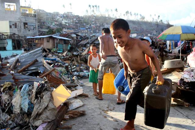 FILE PHOTO: Isang batang  masayang nag-iigib ng tubig sa isang pamayanan sa Tacloban na sinalanta ng Bagyong Yolanda noong 2013. (Julius Castroverde / Photoville International)