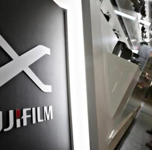 A visitor looks at Fujifilm's digital cameras at the Camera & Photo Imaging Show 2013 in Yokohama, south of Tokyo January 31, 2013. REUTERS/YUYA SHINO