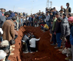 People bury the bodies of eight Hazzm brigade fighters, who were killed during clashes with al Qaeda's official Syria wing Nusra Front fighters in Reef al-Mohandeseen al-Thani and the Mashtal area, in Al-atarib Aleppo countryside February 28, 2015. CREDIT: REUTERS/ABDALGHNE KAROOF