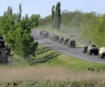 Military vehicles drive along a road at the Russian southern town of Matveev Kurgan, near the Russian-Ukrainian border in Rostov region, Russia, May 24, 2015. Picture taken May 24, 2015. REUTERS/Stringer