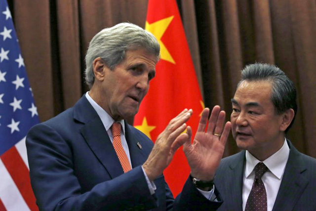 U.S. Secretary of State John Kerry (L) speaks with Chinese Foreign Minister Wang Yi prior to their meeting in Beijing, China, May 16, 2015. REUTERS/Kim Kyung-Hoon