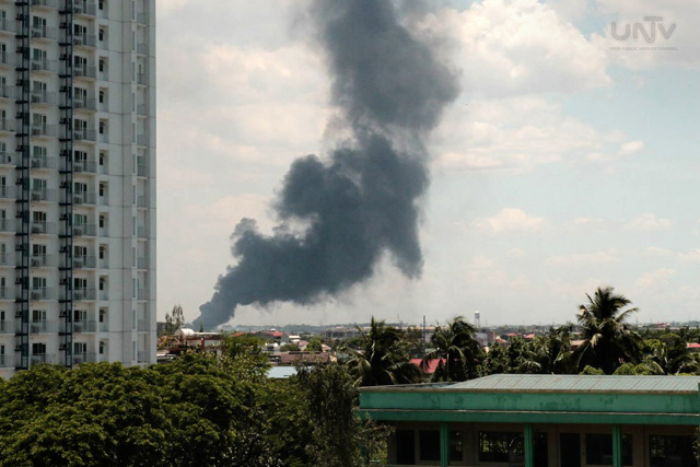 Ang sunog sa factory tsinelas sa Valenzuela nitong Miyerkules ng tanghali na abot-tanaw mula sa isang mall sa Brgy. North Triangle, Quezon City.  (CYRON MONTON / Photoville International)