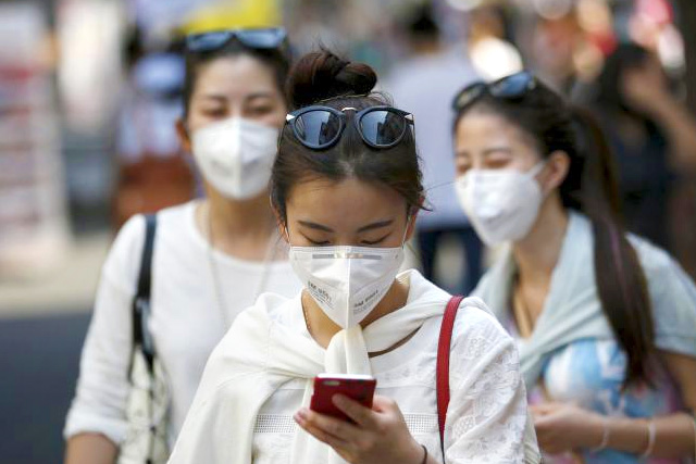 A tourist wearing a mask to prevent contracting Middle East Respiratory Syndrome (MERS) uses her mobile phone at Myeongdong shopping district in central Seoul, South Korea, June 10, 2015. REUTERS/KIM HONG-JI