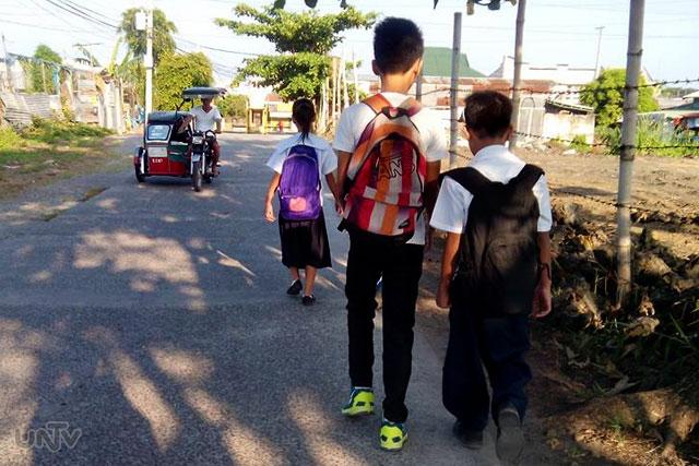 Ilan sa mga mag-aaral na papasok sa kanilang paaralan sa unang araw ng pasukan sa Apalit, Pampanga. (Rovic Balunsay / Photoville International)