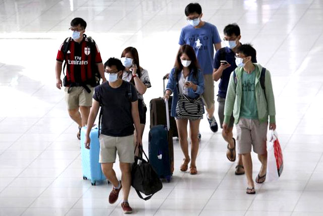 A group of tourists wear masks to prevent contracting Middle East Respiratory Syndrome (MERS) as they arrive at Bangkok's Suvarnabhumi International Airport, Thailand, June 21, 2015. REUTERS/KEREK WONGSA