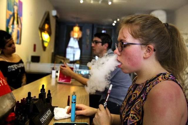 A customer tries different e-cigarette flavors at the Henley Vaporium in New York, June 23, 2015. REUTERS/LUCAS JACKSON